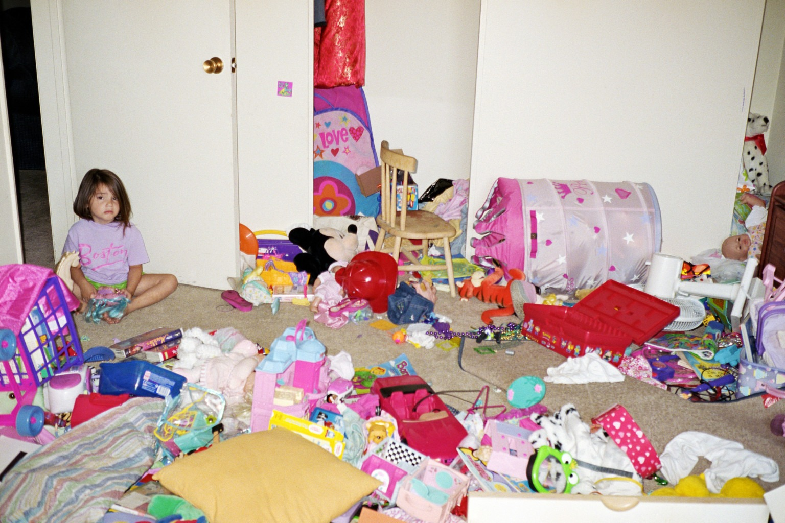 Girl (4-6) sitting on floor in messy room